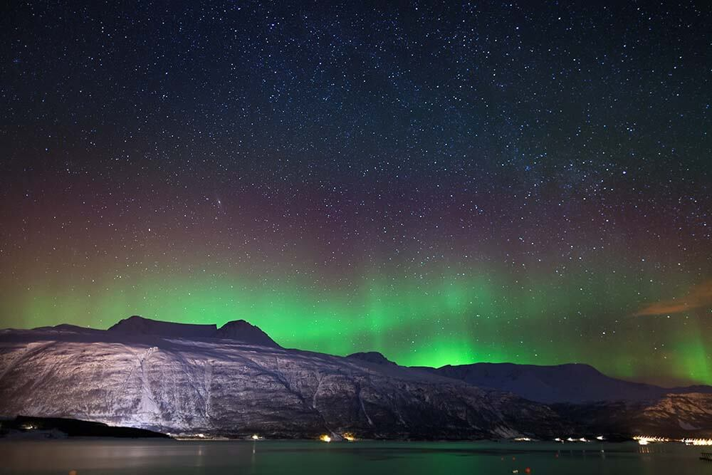 Arctic night in the surroundings of Tromso, Norway : northern lights rising beyond a fjord, enlightening a sky full of stars